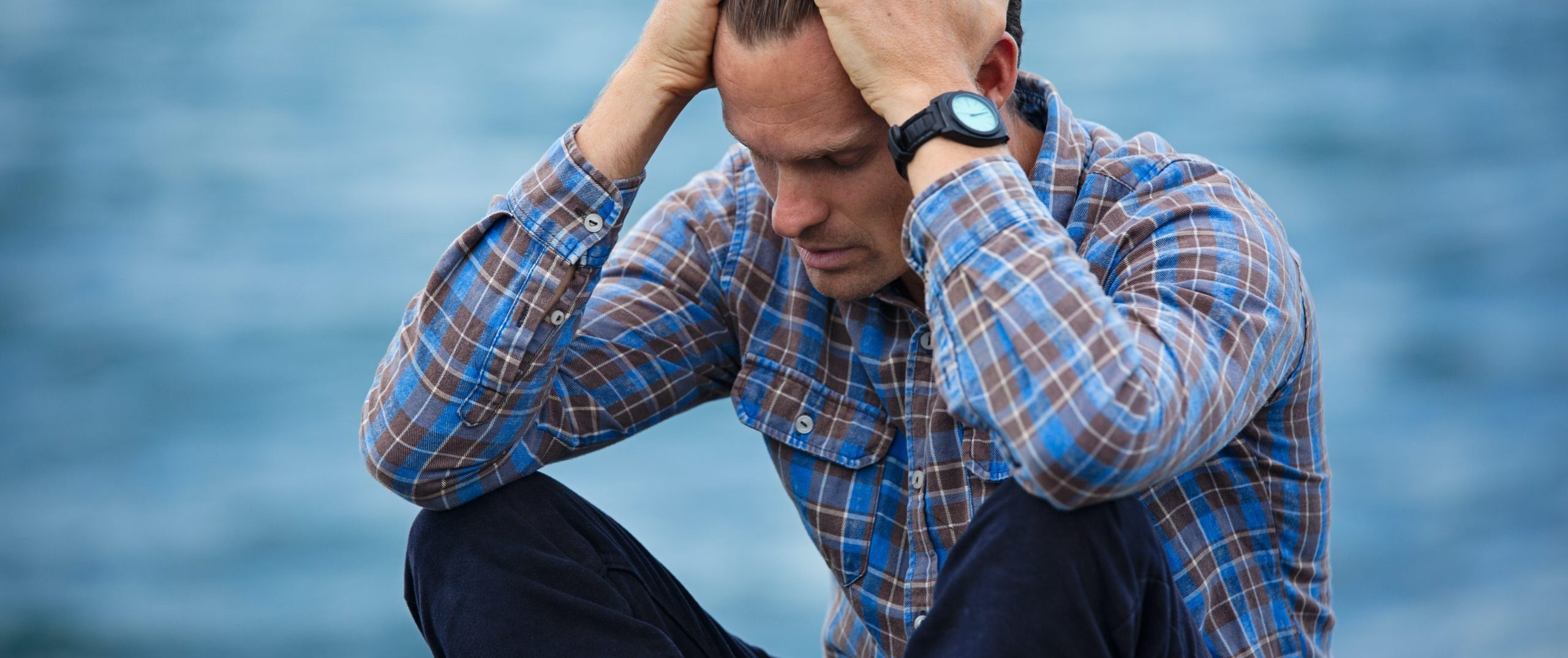 man-in-blue-and-brown-plaid-dress-shirt-touching-his-hair-897817